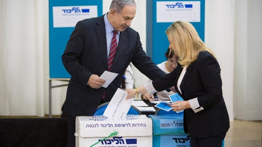 Israeli Prime Minister Benjamin Netanyahu, left, and his wife Sarah cast their vote during Likud party primary elections in Jerusalem, Wednesday, Dec. 31, 2014. Netanyahu is looking to secure a fourth term as premier at a March 17 nation wide vote. (AP Photo/Oded Balilty)