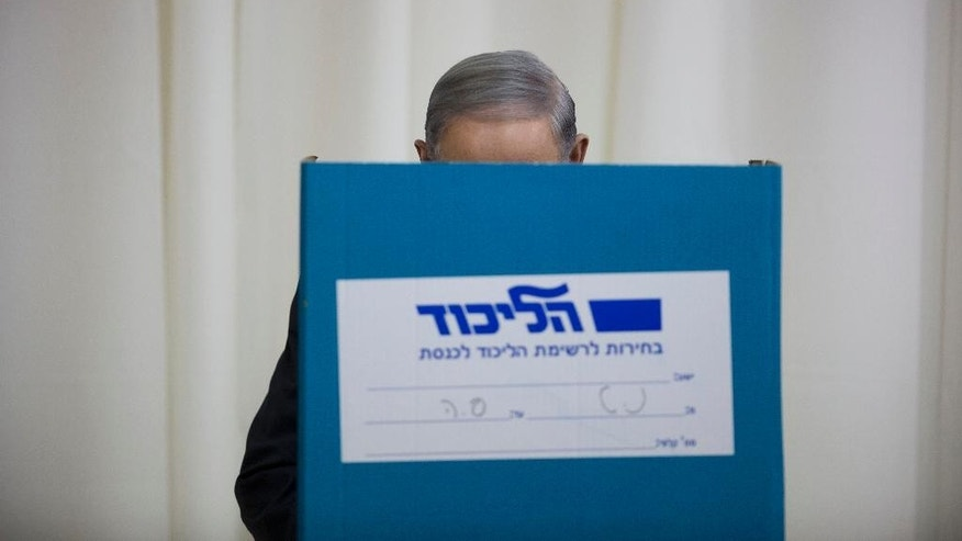 Israeli Prime Minister Benjamin Netanyahu casts his vote during Likud party primary elections in Jerusalem, Wednesday, Dec. 31, 2014. Netanyahu is looking to secure a fourth term as premier at a March 17 nation wide vote. (AP Photo/Oded Balilty)