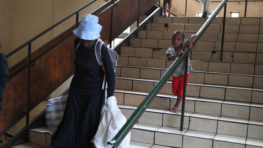 A woman with her belongings in bags leaves the the dilapidated Central Methodist Church in downtown Johannesburg Wednesday, Dec. 31, 2014. The church has offered shelter for those who fled neighboring Zimbabwe and other troubled African countries, as well as South Africa's own homeless. Refugees now face eviction from the shelter that has been home to thousands of desperate people over the past 14 years, church officials say they can no longer afford the wear and tear on the building or the water and electricity bills incurred by the refugees.  (AP Photo/Denis Farrell)