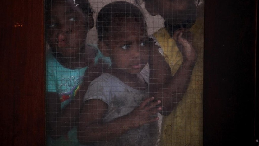Children look through a glass door inside the dilapidated Central Methodist Church in downtown Johannesburg Wednesday, Dec. 31, 2014. The church has offered shelter for those who fled neighboring Zimbabwe and other troubled African countries, as well as South Africa's own homeless. Refugees now face eviction from the shelter that has been home to thousands of desperate people over the past 14 years, church officials say they can no longer afford the wear and tear on the building or the water and electricity bills incurred by the refugees.  (AP Photo/Denis Farrell)