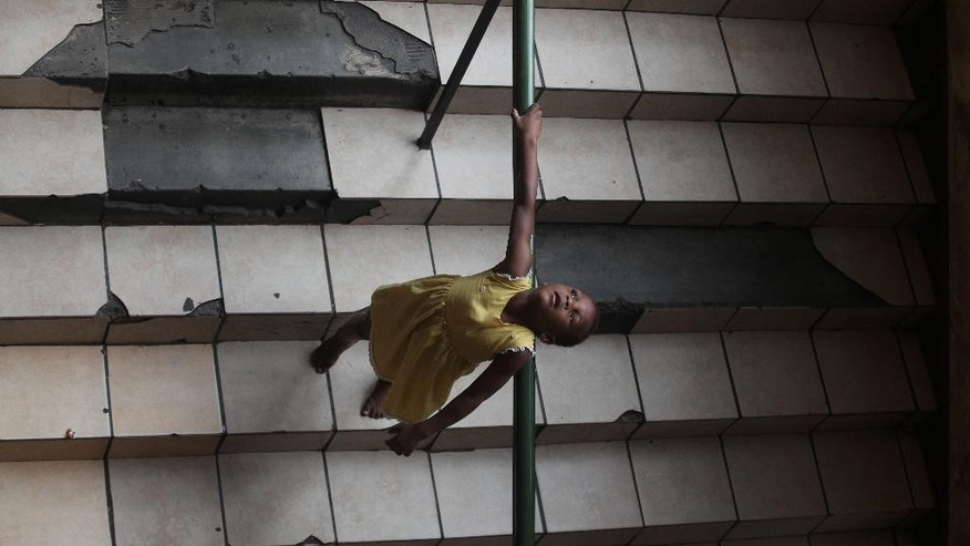 A child plays on steps inside the dilapidated Central Methodist Church in downtown Johannesburg Wednesday, Dec. 31, 2014. The church has offered shelter for those who fled neighboring Zimbabwe and other troubled African countries, as well as South Africa's own homeless. Refugees now face eviction from the shelter that has been home to thousands of desperate people over the past 14 years, church officials say they can no longer afford the wear and tear on the building or the water and electricity bills incurred by the refugees.  (AP Photo/Denis Farrell)