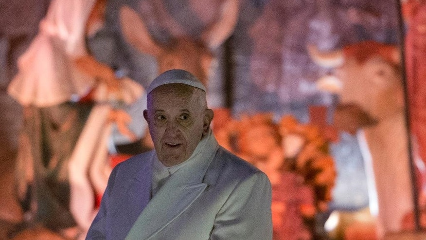 Pope Francis leaves after visiting the nativity scene set in St. Peter's Square after celebrating Mass in St. Peter's Basilica at the Vatican, Wednesday, Dec. 31, 2014. The traditional Mass on Dec. 31 contains the thanksgiving hymn ''Te Deum' for the ending year and is the last public appearance of the pope in 2014. (AP Photo/Andrew Medichini)