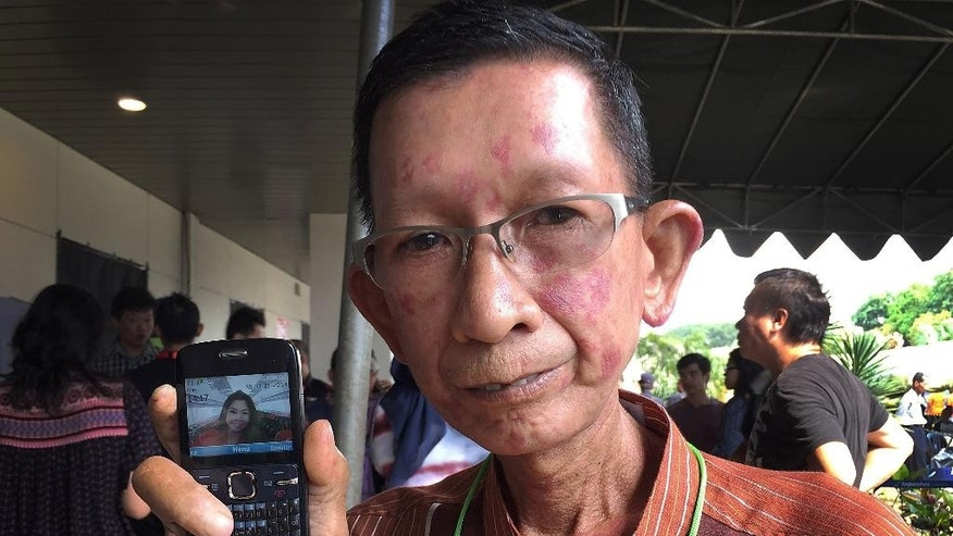 Haidar Fauzie, 60, holds up a picture of his daughter Khairunnisa Haidar, 22, who was a flight attendant on the AirAsia Flight 8501, at Juanda International Airport in Surabaya, East Java, Indonesia, Wednesday, Dec. 31, 2014. As searchers began recovering bodies and debris from Java Sea waters, relatives and loved ones recalled the stories of some of the passengers aboard AirAsia Flight 8501, which crashed Sunday. (AP Photo/Eileen Ng)