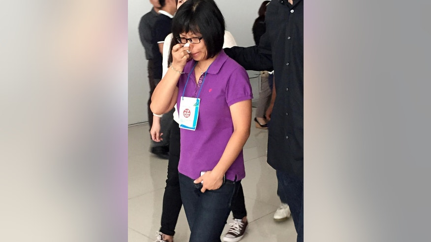 Linca Gonimasela, who lost her 13-year-old son on the AirAsia flight 8510, Adrian Fernando, who had gone to join Linca's aunt and uncle for a vacation in Singapore, wipes her tears at Juanda International Airport in Surabaya, East Java, Indonesia, Wednesday, Dec. 31, 2014. As searchers began recovering bodies and debris from Java Sea waters, relatives and loved ones recalled the stories of some of the passengers aboard AirAsia Flight 8501, which crashed Sunday. (AP Photo/Eileen Ng)