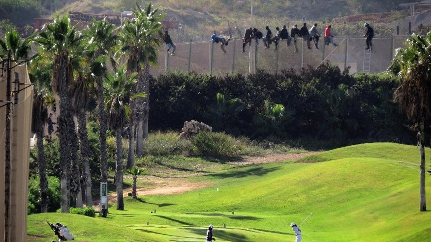 In this photo taken on October 22, 2014, a golfer hits a  shot as sub-Saharan migrants sit atop of a fence that divides Morocco and the Spanish enclave of Melilla during an attempt to cross into Spanish territory in Melilla. (AP Photo/Jose Palazon)
