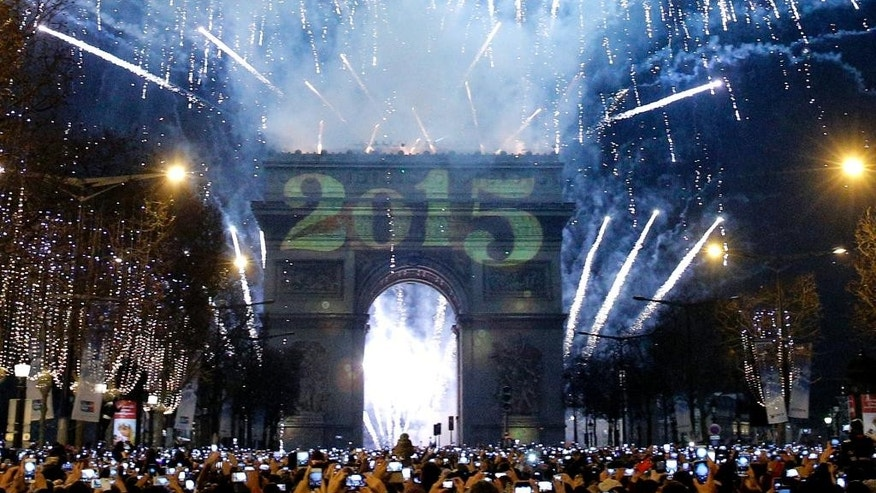 Revelers photograph fireworks over the Arc de Triomphe as they celebrate the New Year's Eve on the Champs Elysees avenue in Paris, France, Thursday, Jan. 1, 2015. (AP Photo/Christophe Ena)