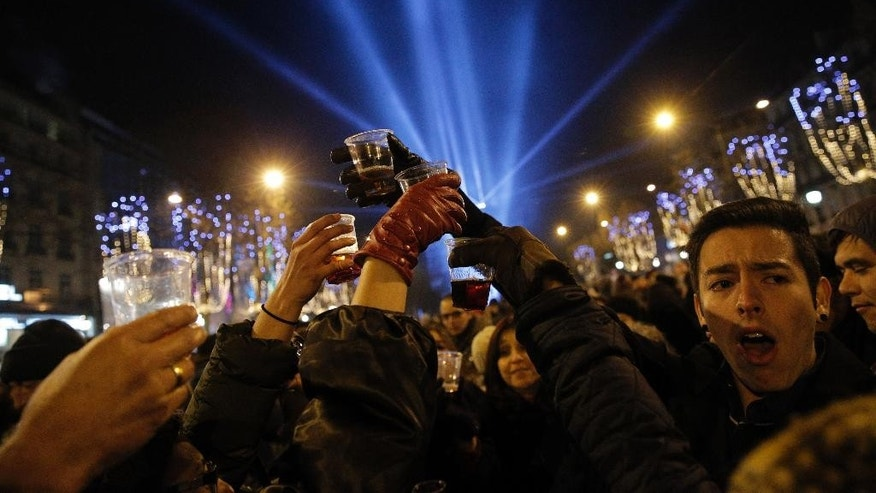 Revellers celebrate the New Year's Eve on the Champs Elysees avenue in Paris, France, Thursday, Jan. 1, 2015. The Arc de Triomphe is illuminated in the background. (AP Photo/Christophe Ena)