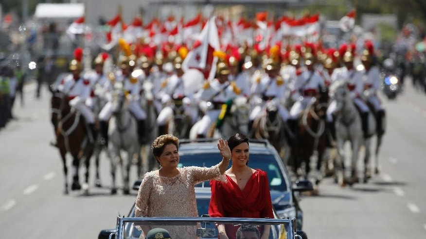 Brazil's President Dilma Rousseff, left, waves to the crowd, accompanied by her daughter Paula Rousseff Araujo, aboard a Rolls Royce on their way to the National Congress during her inauguration ceremony in Brasilia, Brazil, Thursday, January 1, 2015. Rousseff was re-elected to a second term to lead the world's fifth-largest nation after beating opposition contender Aecio Neves. (AP Photo/Leo Correa)