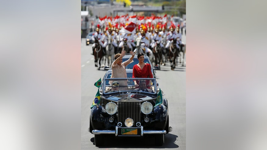 Brazil's President Dilma Rousseff, left, waves to the crowd, accompanied by her daughter Paula Rousseff Araujo, in a Rolls Royce on their way to the National Congress during her inauguration ceremony in Brasilia, Brazil, Thursday, January 1, 2015. Rousseff was re-elected to a second term to lead the world's fifth-largest nation after beating opposition contender Aecio Neves. (AP Photo/Leo Correa)
