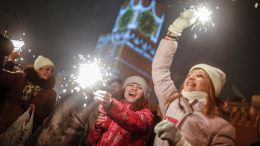 FILE - In this Thursday, Jan. 1, 2015 file photo, people light sparklers as they celebrate the New Year at the Red Square in Moscow, Russia. A recent Associated Press-NORC Center for Public Affairs Research poll showed that Russians who rely on state TV for their news think significantly more highly of President Vladimir Putin than those who tap other sources, but for both sectors the support for Putin is resoundingly strong -- 84 percent and 73 percent respectively. (AP Photo/Denis Tyrin, file)