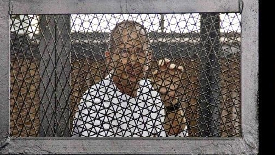 FILE - This combination of three 2014 file photos shows from left, Canadian-Egyptian journalist Mohamed Fahmy, Al-Jazeera's Australian correspondent Peter Greste, and Egyptian producer Baher Mohamed at a court room during their trial in Cairo, Egypt. An appeals court in Egypt on Thursday, Jan. 1, 2015 has ordered a retrial in the case of the three imprisoned Al-Jazeera English journalists. (AP Photo/Ahmed Abd El Latif, Hamada Elrasam, File) EGYPT OUT