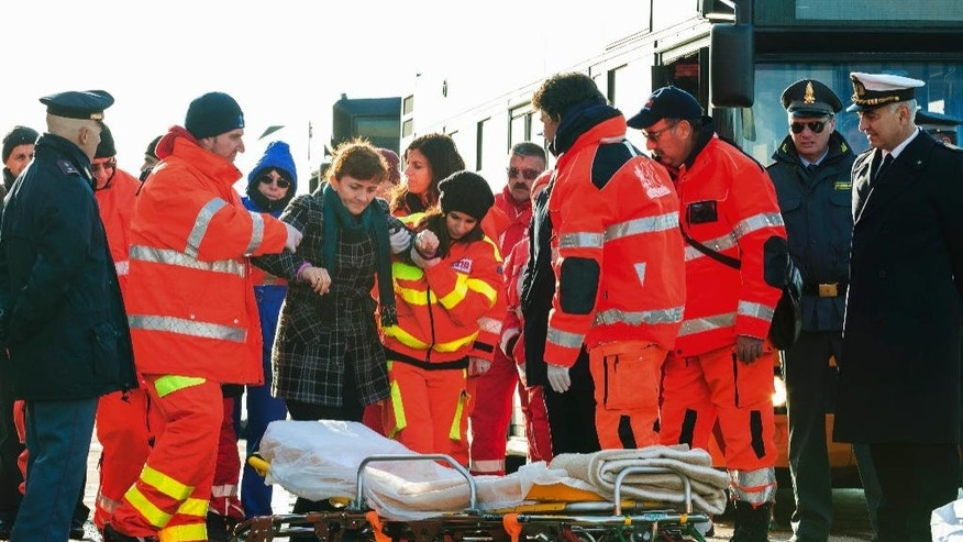 An injured passenger is being eased to a stretcher as she and some 40 of the survivors of the Norman Atlantic ferry fire, finally stepped ashore, in the port of Taranto, Italy, Wednesday, Dec. 31, 2014. They arrived by one of the cargo ships that took aboard passengers from the flaming, smoke-shrouded ferry in the first hours after the blaze down in the car deck sent people, shaken out of their sleep, to scrambling for their lives and take shelter -- in freezing cold, pelted by rain and buffeted by gale-force wind on the top, uncovered deck. (AP Photo/Cosimo Calabrese)