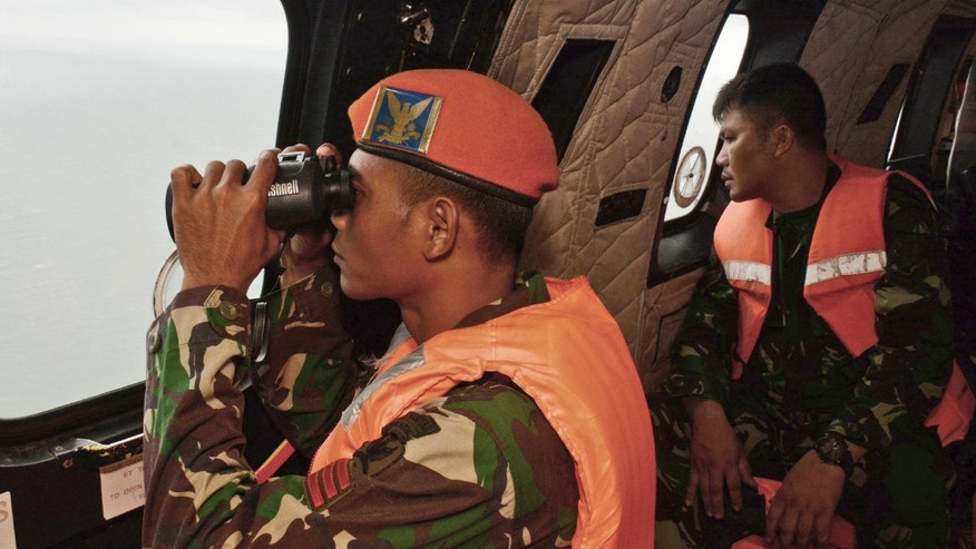 Jan. 1, 2015: A crew member of an Indonesian Air Force Super Puma helicopter of 6th Air Squadron uses a pair of binoculars to scan the horizon during a search operation for the victims of AirAsia Flight 8501 over Java Sea, Indonesia