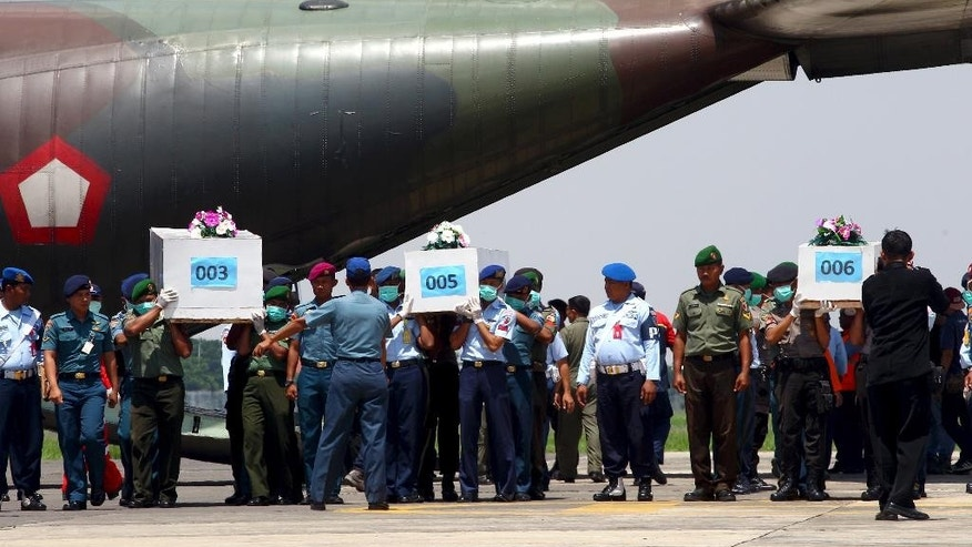 "Indonesian soldiers carry coffins containing victims of AirAsia Flight 8501 upon arrival at Indonesian Military Air Force base in Surabaya, Indonesia, Thursday, Jan. 1, 2015. A much needed break in the weather gave searchers a window Thursday to ""fight with full force"" to find the victims of the flight, with officials also hustling to locate the plane's fuselage after it crashed into the Java Sea four days ago. (AP Photo/Firdia Lisnawati)"