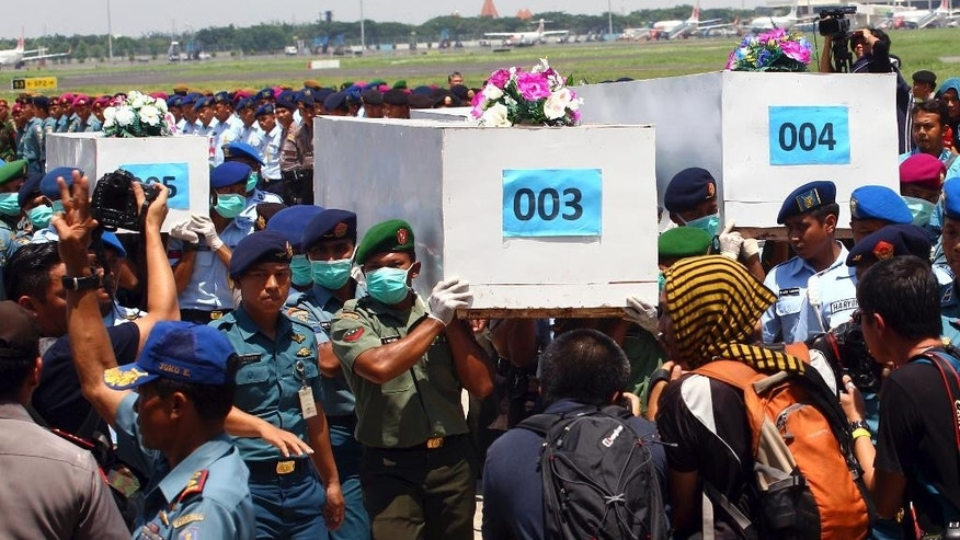 "Indonesian soldiers carry coffins containing the bodies of victims of AirAsia Flight 8501 upon arrival at Indonesian Military Air Force base in Surabaya, Indonesia, Thursday, Jan. 1, 2015. A much needed break in the weather gave searchers a window Thursday to ""fight with full force"" to find the victims of the flight, with officials also hustling to locate the plane's fuselage after it crashed into the Java Sea four days ago. (AP Photo/Firdia Lisnawati)"