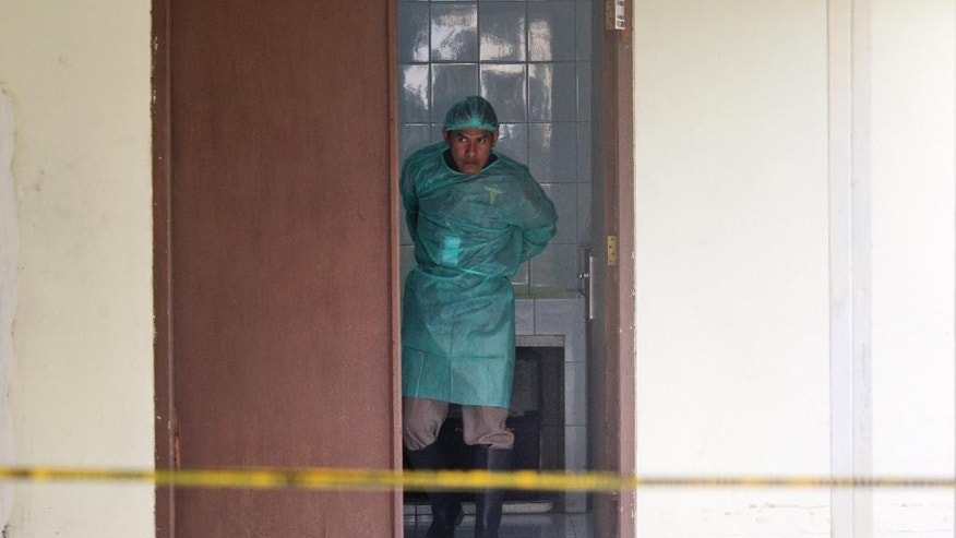 A medical worker dons his protective clothing at the morgue where the bodies of the victims of AirAsia Flight 8501 are waiting to undergo identification process at the police hospital in Surabaya, East Java, Indonesia, Thursday, Jan. 1, 2015. The weather improved as the search resumed Thursday for the victims with officials trying to locate the fuselage of the plane that crashed in the sea four days ago. (AP Photo/Trisnadi)