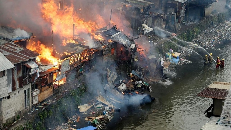 Firefighters fight the fire at shanties from a creek in suburban Quezon city, north of Manila, Philippines during an early morning fire Thursday, Jan. 1, 2015. The huge fire, believed to have been ignited by firecrackers, razed hundreds of shanties in a creekside slum in metropolitan Manila Thursday in one of more than a dozen fires reported across the country as Filipinos welcomed the New Year. (AP Photo/Bullit Marquez)