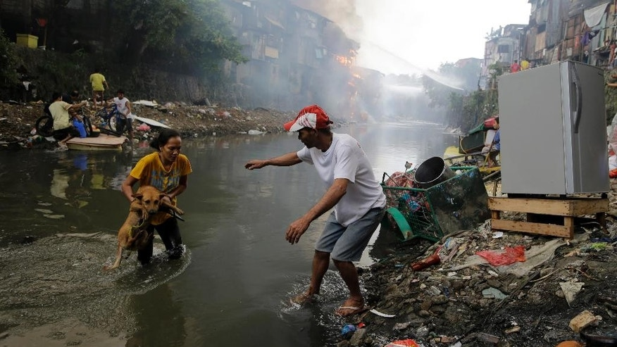 Residents save their pet dog as a huge fire rages along a creek in suburban Quezon city north of Manila, Philippines, on the New Year's day Thursday, Jan. 1, 2015. A huge fire, believed to have been ignited by firecrackers, razed hundreds of shanties in the slum Thursday in one of more than a dozen fires reported across the country as Filipinos welcomed the New Year. (AP Photo/Bullit Marquez)