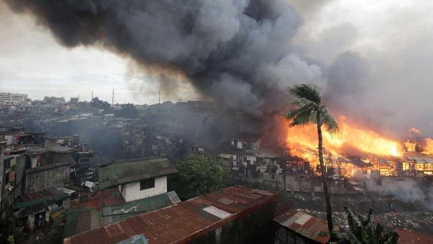 A huge fire engulfs houses along a creek in suburban Quezon city, north of Manila, Philippines on New Year's day Thursday, Jan. 1, 2015. A huge fire, believed to have been ignited by firecrackers, razed hundreds of shanties in the creekside slum Thursday in one of more than a dozen fires reported across the country as Filipinos welcomed the New Year. (AP Photo/Bullit Marquez)