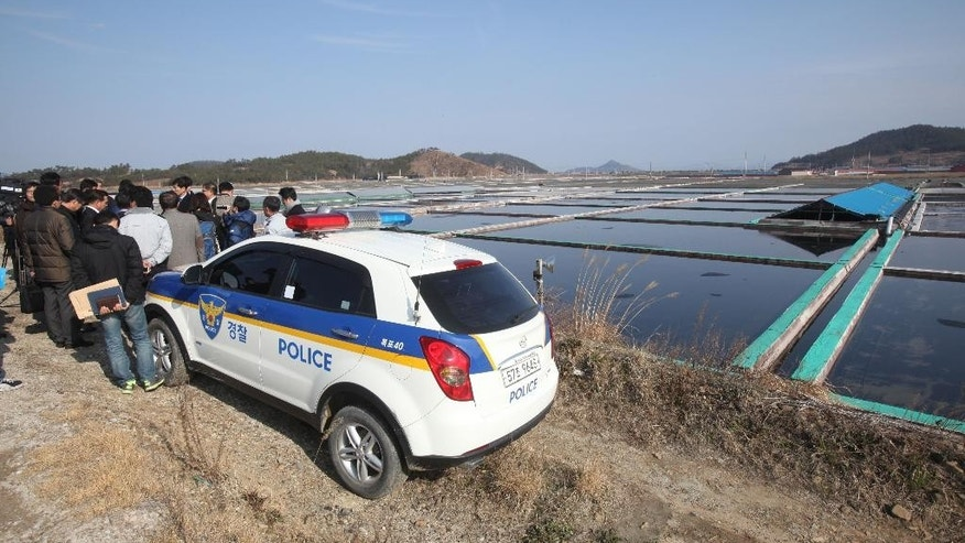 In this Feb. 19, 2014, lawmakers and human right activists look at salt farms as a part of human rights inspection on Sinui Island, South Korea. Slavery thrives on this chain of rural islands off South Korea's rugged southwest coast, nurtured by a long history of exploitation and the demands of trying to squeeze a living from the sea. Five times during the last decade, revelations of slavery involving the disabled have emerged, each time generating national shame and outrage. (AP Photo/Ahn Young-joon)
