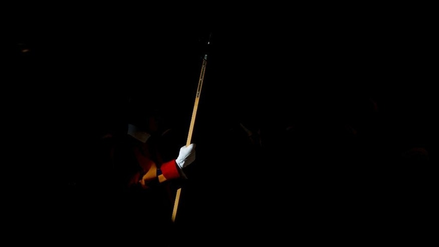 A Swiss guards hold his lance as he attends a New Year mass celebrated by Pope Francis in St. Peter's Basilica at the Vatican, Thursday, Jan. 1, 2015. (AP Photo/Andrew Medichini)