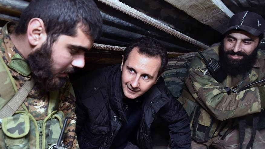 In this Wednesday, Dec. 31, 2014 photo released by the Syrian official news agency SANA, Syrian President Bashar Assad, center, speaks with Syrian troops during his visit to the front line in the eastern Damascus district of Jobar, Syria. Assad has made a rare visit to the frontline spending New Year's Eve with his troops in a tense eastern Damascus neighborhood. (AP Photo/SANA)