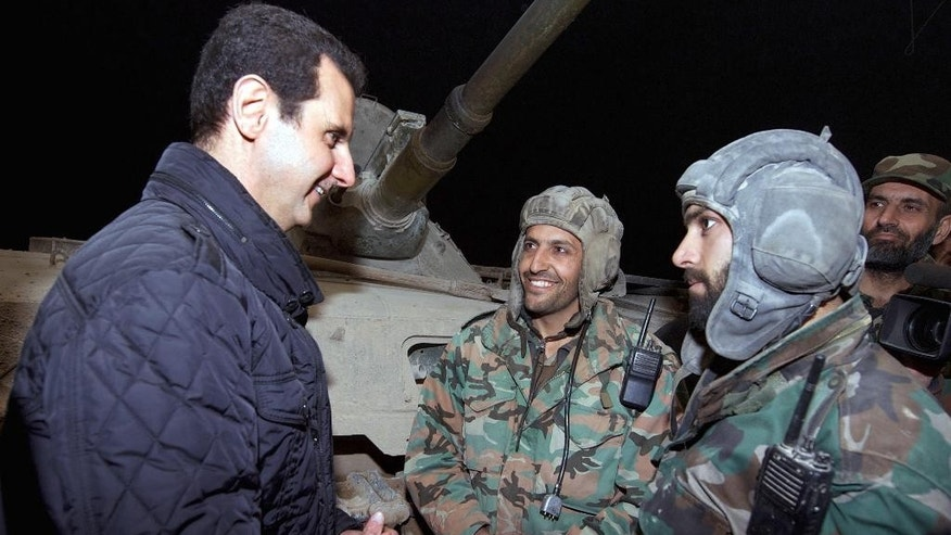 In this Wednesday, Dec. 31, 2014 photo released by the Syrian official news agency SANA, Syrian President Bashar Assad, left, speaks with Syrian troops during his visit on the front line in the eastern Damascus district of Jobar, Syria. Assad has made a rare visit to the front line of his country's civil war, spending New Year's Eve with his troops in a tense eastern Damascus neighborhood. (AP Photo/SANA)