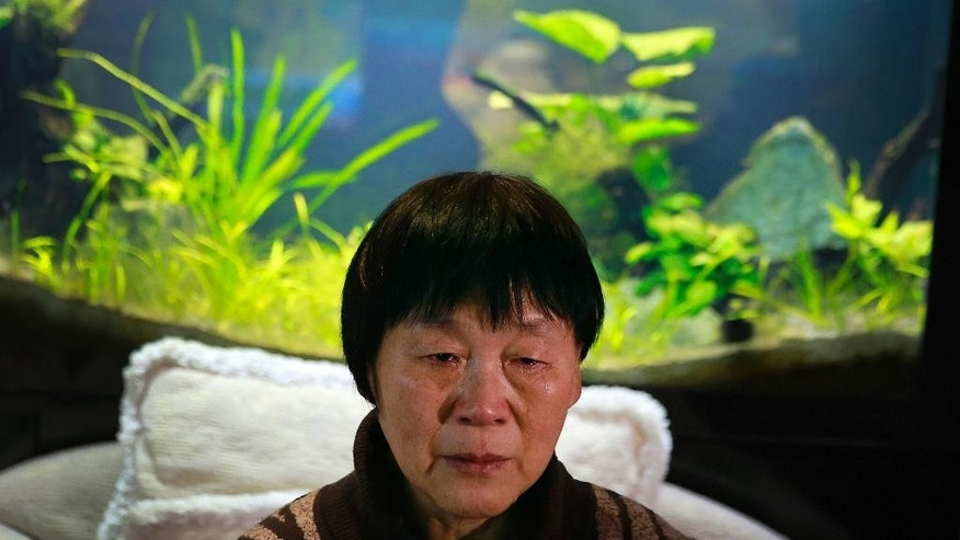 "In this Sunday, Dec. 28, 2014 photo, Dai Shuqin, whose sister was aboard Malaysia Airlines Flight 370 that went missing on March 8, 2014, weeps as she watches TV news about missing AirAsia Flight 8501, during a year-end gathering with others at a house in Beijing, China. Images of bodies and wreckage floating in Indonesian waters gave relatives of those lost aboard AirAsia Flight 8501 anguish and grief, but they also provided the answers that other families have sought in vain for nearly 10 months. ""We have been living in anxiety, fear and hate, and our lives have been utterly messed up, but we as ordinary people are unable to do anything,"" said Dai. (AP Photo/Andy Wong)"