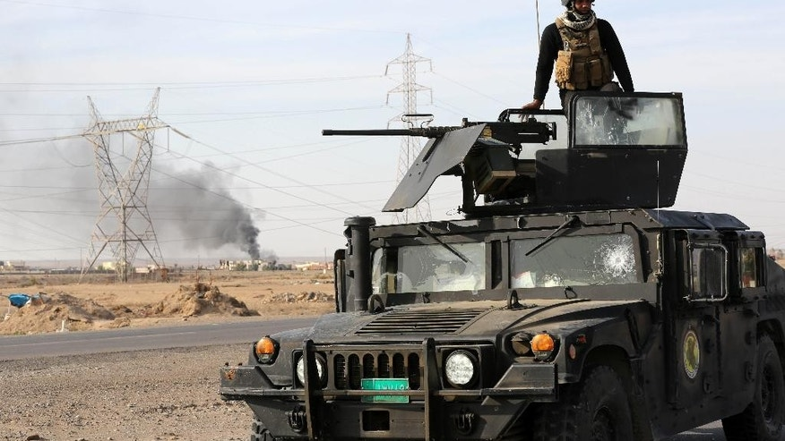 In this Monday, Dec. 8, 2014 photo, Iraqi security forces deploy in a military operation to regain control of the villages around the town of Beiji, some 250 kilometers (155 miles) north of Baghdad, Iraq. Lt. Gen. Abdul-Wahab al-Saadi had 225 fighters, a single Abrams tank, a pair of mortars, two artillery pieces and about 40 armored Humvees when he set out to retake Beiji, a strategic city in northern Iraq captured by Islamic State militants over the summer. (AP Photo/Hadi Mizban)