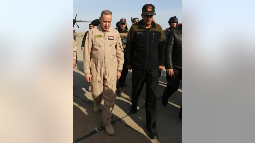 In this Monday, Dec. 8, 2014 photo, Lt. Gen. Abdul-Wahab al-Saadi, right, walks beside Iraqi Defense Minister Khalid al-Obeidi, as he welcomes the minister's visit at a military base inTikrit, 80 miles (130 kilometers) north of Baghdad, Iraq. Al-Saadi set out to retake Beiji, a strategic city in northern Iraq captured by Islamic State militants over the summer. It took 30 days as his force made an agonizingly slow journey for 40 kilometers (25 miles) through roadside bombs and suicide car attacks, then successfully laid siege to the oil refinery city of Beiji. The campaign earned al-Saadi the biggest battlefield victory by Iraqi forces since the military collapsed as Islamic State fighters swept over most of northern and western Iraq in a summer blitz. (AP Photo/Hadi Mizban)