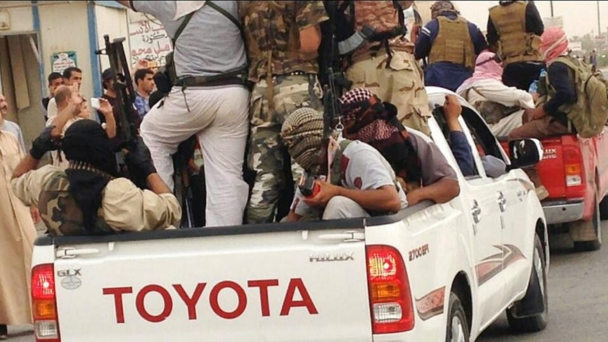 FILE - In this Tuesday, July 29, 2014, file photo, Islamic militants parade in Beiji, some 250 kilometers (155 miles) north of the capital, Baghdad, Iraq. Lt. Gen. Abdul-Wahab al-Saadi then set out to retake Beiji, a strategic city in northern Iraq captured by Islamic State militants over the summer. It took 30 days as his force made an agonizingly slow journey for 40 kilometers (25 miles) through roadside bombs and suicide car attacks, then successfully laid siege to the oil refinery city of Beiji. The campaign earned al-Saadi the biggest battlefield victory by Iraqi forces since the military collapsed as Islamic State fighters swept over most of northern and western Iraq in a summer blitz. (AP Photo, File)