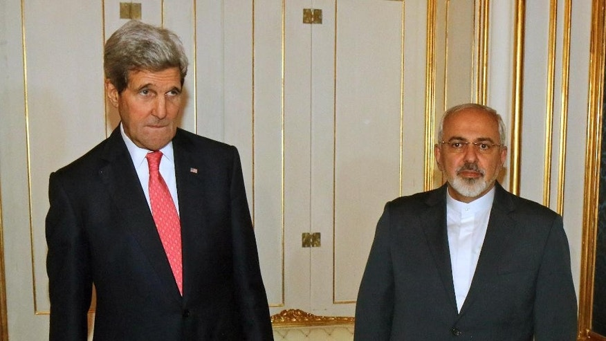 FILE - In this Nov. 23, 2014 file photo, U.S. Secretary of State John Kerry and Iranian Foreign Minister Mohammad Javad Zarif, right, pose for a photograph prior to a bilateral meeting of the closed-door nuclear talks in Vienna, Austria. Diplomats say Iran and the U.S. have tentatively agreed that Tehran will ship to Russia much of the material it could use to manufacture nuclear weapons. (AP Photo/Ronald Zak, Pool-File)