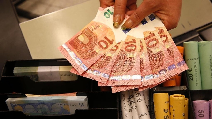Euro coins and banknotes are shown by a salesclerk at a shop in Vilnius, Lithuania, Thursday, Jan. 1, 2015. The Baltic state of Lithuania early Thursday became the 19th European Union member to adopt the joint European currency, the euro. (AP Photo/Mindaugas Kulbis)
