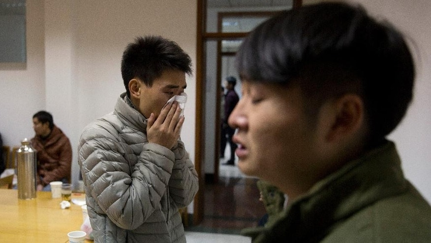 A man who only gave his surname Zhao cries after seeing a photo of his girlfriend Pan Haiqin who was killed in the deadly stampede in Shanghai, China, Friday, Jan. 2, 2015. People unable to contact friends and relatives streamed into hospitals Thursday, anxious for information after a stampede during New Year's celebrations in Shanghai's historic waterfront area killed 36 people in the worst disaster to hit one of China's showcase cities in recent years. (AP Photo/Ng Han Guan)