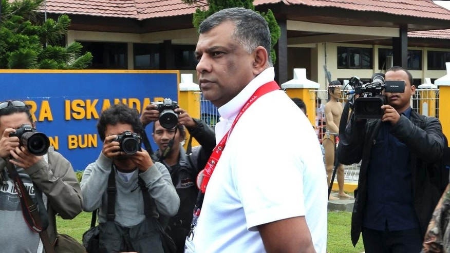 In this Wednesday, Dec. 31, 2014 photo, AirAsia Group CEO Tony Fernandes is surrounded by photographers and TV cameramen as he walks upon his arrival to visit the command center of the search operation for the victims of AirAsia Flight 8501 at the airport in Pangkalan Bun, Indonesia. From the highly visible compassion shown by Fernandes to details such as changing the airline's bright red logo to a somber gray online, experts say the Malaysia-based budget carrier's initial response to the tragedy is a textbook example of how to communicate in a crisis. (AP Photo/Tatan Syuflana)