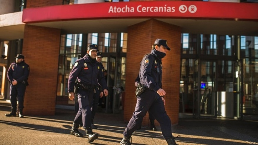 Police guard outside Atocha train station during a bomb threat in Madrid, Spain, Friday, Jan. 2, 2015. Police have evacuated people from Madrids Atocha train station and halted trains in and out of the busy city-center station following a bomb threat that police says was a hoax. (AP Photo/Andres Kudacki)