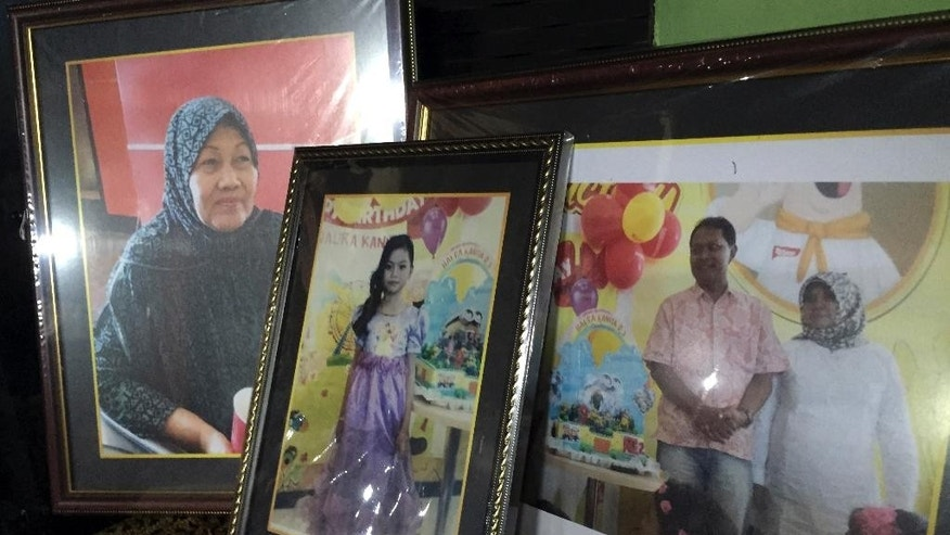 In this Thursday, Jan. 1, 2015 photo, framed pictures, from left, of Soemanik Saeran, 64, Naura Kanita Rosada Suseno, 9, and Djoko Suseno, 43, with his wife Hayati Lutfiah Hamid, 39, are displayed in the home of Soemanik where relatives and friends gathered for nightly prayers, in Surabaya, Indonesia. Prayers of hope that the four were still alive have since given way to prayers that their bodies will be recovered quickly, after wreckage of AirAsia Flight 8501 and the first bodies were discovered by rescuers Tuesday. (AP Photo/Eileen Ng)