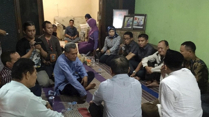 In this Thursday, Jan. 1, 2015 photo, relatives and friends gather for nightly prayers at the home of Soemanik Saeran, 64, one of the victims that was traveling with three of her family members on AirAsia Flight 8501, in Surabaya, Indonesia. All week relatives and friends sat on prayer mats laid at the porch for their nightly intercession. Prayers that their loved ones would be found alive have given away to prayers that their bodies will be recovered quickly. (AP Photo/Eileen Ng)