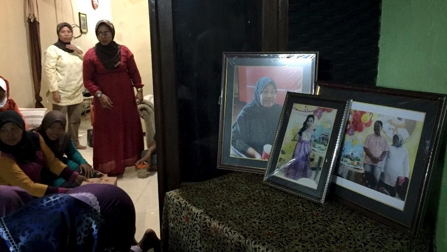 In This Thursday Jan. 1, 2015 photo, framed pictures, from left, of Soemanik Saeran, 64, Naura Kanita Rosada Suseno, 9, and Djoko Suseno, 43 with his wife Hayati Lutfiah Hamid, 39, are displayed in the home of Soemanik where relatives and friends have gathered for nightly prayers, in Surabaya, Indonesia. PPrayers of hope that the four were still alive have since given way to prayers that their bodies will be recovered quickly, after wreckage of AirAsia Flight 8501 and the first bodies were discovered by rescuers Tuesday. (AP Photo/Eileen Ng)