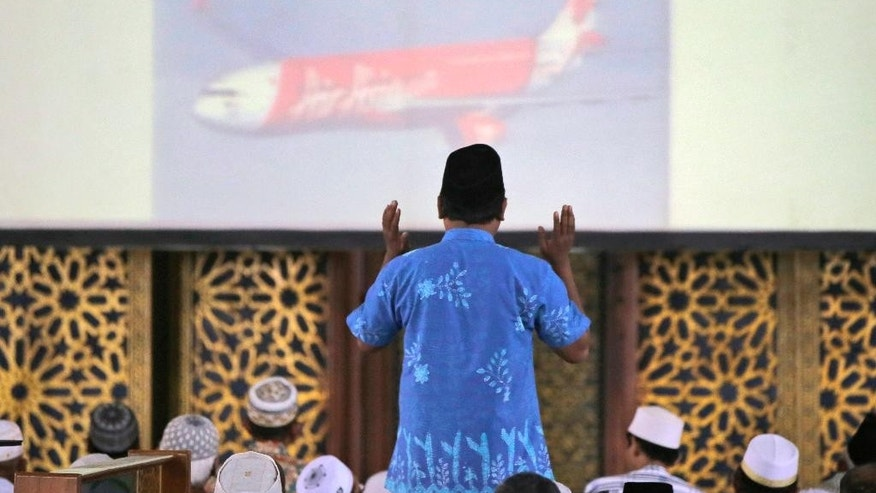 An Indonesian Muslim man prays during a special prayer for the victims of AirAsia Flight 8501 at Al Akbar Mosque in Surabaya, East Java, Indonesia, Friday, Jan. 2, 2015. More ships arrived Friday with sensitive equipment to hunt for the fuselage of the flight and the more than 145 people still missing since it crashed into the sea five days ago. (AP Photo/Dita Alangkara)
