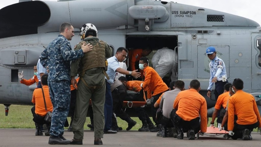 National Search and Rescue Agency personnel carry the body of a victim aboard the ill-fated AirAsia Flight 8501 from a U.S. Navy helicopter that belongs to USS Sampson upon arrival at the airport in Pangkalan Bun, Indonesia, Friday, Jan. 2, 2015. A massive hunt for the 162 victims of the flight resumed in the Java Sea on Wednesday, with six bodies, including a flight attendant identified by her trademark red uniform, recovered. But wind, strong currents and high surf hampered recovery efforts as distraught family members anxiously waited to identify their loved ones.  (AP Photo/Achmad Ibrahim)
