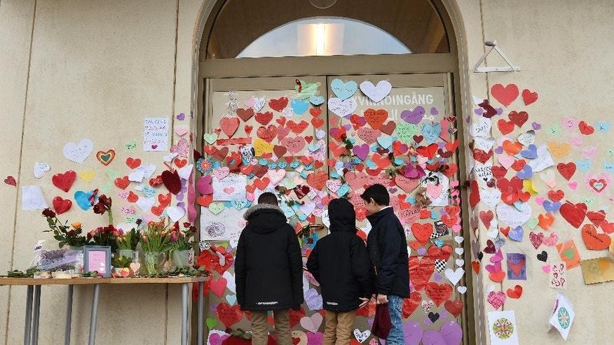 Boys read the messages placed at the entrance of a mosque by neighbors pledging their support after an attack, in Uppsala, Sweden, Friday, Jan.  2, 2015.  The mosque suffered a firebomb attack on Jan. 1, one of three arson attacks targeting the Muslim community in Sweden since Christmas Day. (AP Photo/Anders Wiklund)  SWEDEN OUT