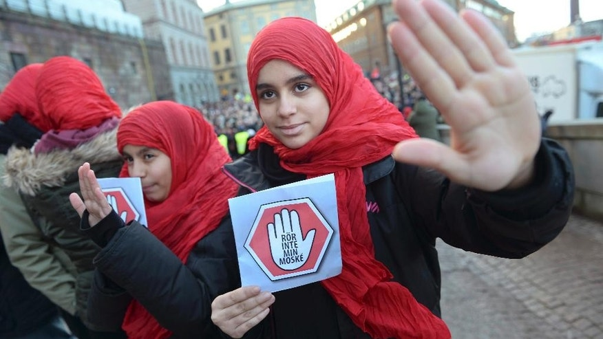 "Two young girls carrying leaflets saying ""don't touch my mosque"" participate in a demonstration at the  parliament in Stockholm on Friday  Jan. 2, 2015. Three mosques have suffered arson attacks in Sweden since Christmas Day. (AP Photo/Fredrik Sandberg) SWEDEN OUT"