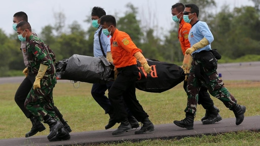 National Search And Rescue Agency (BASARNAS) personnel carry the body of a victim on board the ill-fated AirAsia Flight 8501, from a helicopter upon arrival at the airport in Pangkalan Bun, Indonesia, Saturday, Jan. 3, 2015. After nearly a week of searching for the victims of AirAsia Flight 8501, rescue teams battling monsoon rains had their most successful day yet, more than tripling the number of bodies pulled from the Java Sea, some still strapped to their seats. (AP Photo/Tatan Syuflanai)
