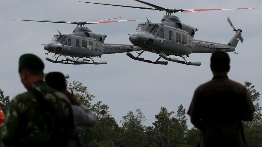 Indonesia Navy helicopters airlifting the bodies of the victims on board the ill-fated AirAsia Flight 8501, arrive at the airport in Pangkalan Bun, Indonesia, Saturday, Jan. 3, 2015. After nearly a week of searching for the victims of AirAsia Flight 8501, rescue teams battling monsoon rains had their most successful day yet, more than tripling the number of bodies pulled from the Java Sea, some still strapped to their seats. (AP Photo/Tatan Syuflanai)