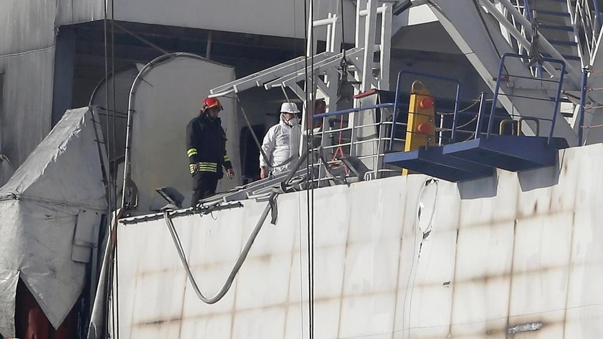 Italian firemen work on the Norman Atlantic ferry after it was towed into the port of Brindisi, southern Italy, Saturday, Jan. 3, 2015. Wearing gas masks against the smoke, Italian firefighters and investigators boarded the charred Norman Atlantic ferry on Friday and retrieved a data recorder they hope will help them discover what caused a deadly blaze. Some parts of the ferry are still burning making difficoult the search for any more bodies in the maritime disaster that has already killed 11 people. (AP Photo/Antonio Calanni)