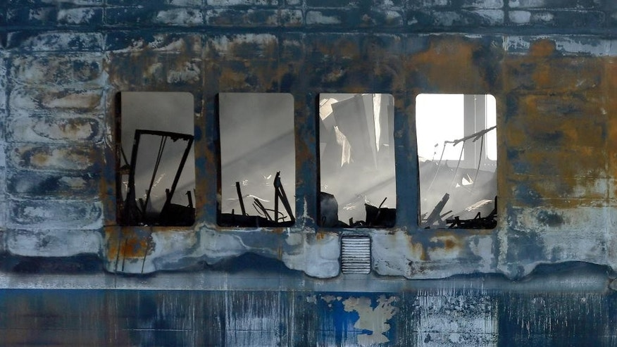 Light streams through a window of the Norman Atlantic ferry as it is being towed into the port of Brindisi, Italy, Friday, Jan. 2, 2015. The blaze that broke out Sunday and torched the ferry has killed at least 11 people and authorities prepared to search it for possible more dead. Italy says 477 people were rescued, most by helicopters that plucked survivors off the top deck in gale-force winds and carried them to nearby boats. (AP Photo/Antonio Calanni)