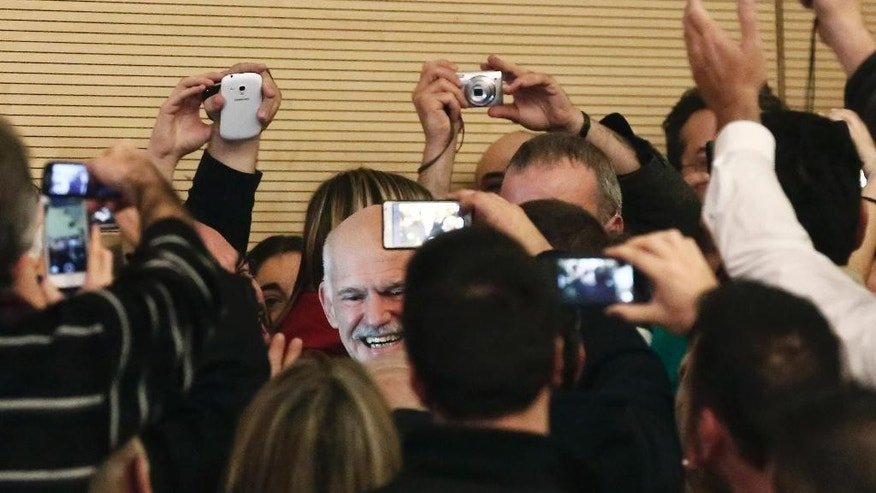 Former Greek Prime Minister George Papandreou gestures to a crowd of supporters gathered in Athens, on Saturday Jan. 3, 2015. Papandreou announced the formation of a new party, the Movement of Democrat Socialists, which will contest the Jan. 25 election.(AP Photo/Petros Giannakouris)