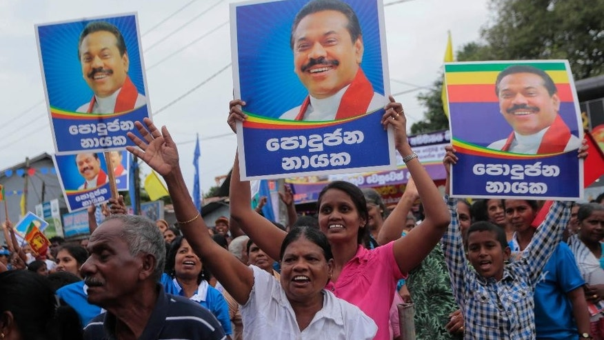 "In this Dec. 24, 2014 photo, supporters hold portraits of Sri Lankan President Mahinda Rajapaksa and cheer during an election campaign rally in Colombo, Sri Lanka. He was the president hailed as a king after crushing the Tamil Tiger rebels in 2009 and ending the island nation's 25-year civil war. But an internal revolt now threatens Rajapaksa's hold on power. Health Minister Maithripala Sirisena, a close Rajapaksa aide and the No. 2 person in the president's Freedom Party, defected in a secretly choreographed news conference in late November, announcing he would run as an opposition candidate in the  Jan. 8, 2015 election. Posters read "" Leader of the Common."" (AP Photo/Eranga Jayawardena)"