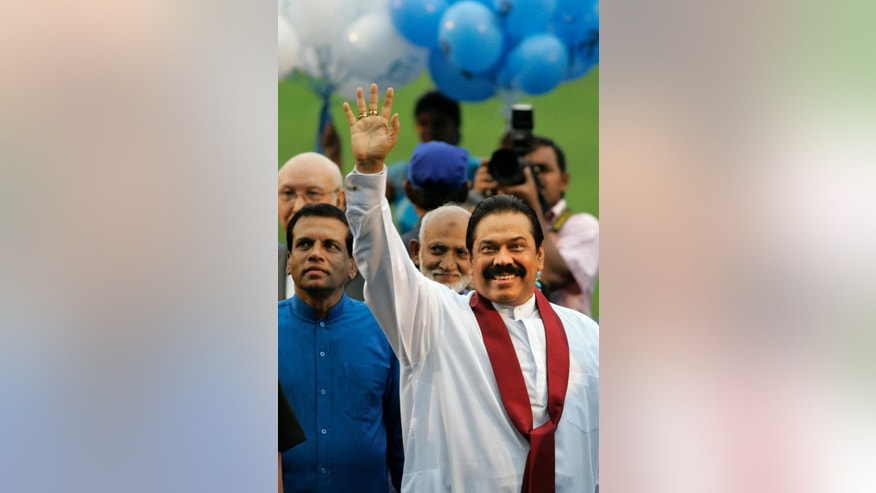 FILE – In this Nov. 15, 2009 file photo, Sri Lankan President Mahinda Rajapaksa, right, waves to his supporters as Sri Lanka Freedom Party (SLFP) General Secretary Maithripala Sirisena, left, looks on during a party convention in Colombo, Sri Lanka. He was the president hailed as a king after crushing the Tamil Tiger rebels in 2009 and ending the island nation's 25-year civil war. But an internal revolt now threatens Rajapaksa's hold on power. Health Minister Sirisena, a close Rajapaksa aide and the No. 2 person in the president's Freedom Party, defected in a secretly choreographed news conference in late November, 2014, announcing he would run as an opposition candidate in the Jan. 8, 2015 election. (AP Photo/Eranga Jayawardena, File)